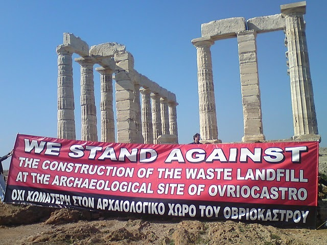 photo : piliers de ruines grecques authentiques, devant lequel des tiennent une grande banderole : We stand against the construction of the waste landfill at the archaeological site of Ovriocastro.